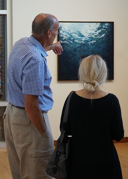 Torrance Combs points out a painting that caught his eye to Janet Berry.