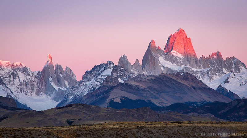 The first light of sunrise illuminates the spire of Mount Fitz Roy in Patagonia, Argentina