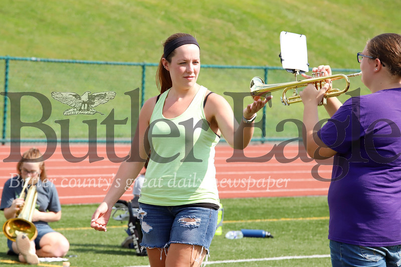 Karns City marching band director Amanda Pivirotto adjusts the stance of a band member during a practice Tuesday at Karns City High School. Seb Foltz/Butler Eagle 082019