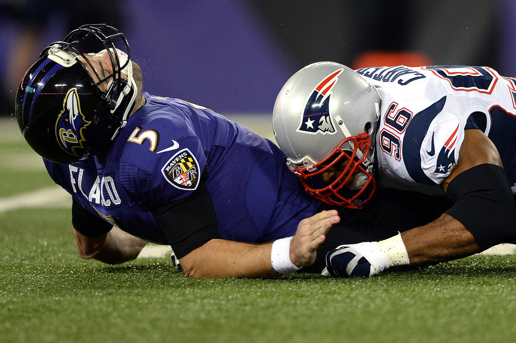 . Quarterback Joe Flacco #5 of the Baltimore Ravens is hit by defensive end Andre Carter #96 of the New England Patriots in the first quarter at M&T Bank Stadium on December 22, 2013 in Baltimore, Maryland. (Photo by Patrick Smith/Getty Images)