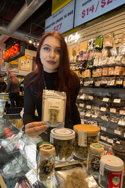 """Seattle has had a reputation as a fairly tolerant city and in 2003 possession and consumption of weed dropped from a higher priority felony to a look-the-other-way misdemeanor. In 2012 Washington voters legalized recreational use of cannabis. One of the first and most successful pot shops to open was Uncle Ike's, which began in Seattle's Central District and soon opened branches on nearby Capitol Hill and somewhat distant Southcenter . Since opening Ike's has sold tens of millions of dollars worth of weed products – more than double any other vendor in the state.  Taxes to the state from the all sales of legalized pot are projected to total $730 million over 2018-19.  At Ike's Central District store, approximately 1000 transactions a day are consumated,  sales associate Adrienne Mischenko showed off some of Ike's massive inventory, which includes budded marijuana """"flower"""", edibles (cookies etc), topicals (oils) and paraphernalia. Mischenko, like the other employees, gets a good wage and full benefits including healthcare."""