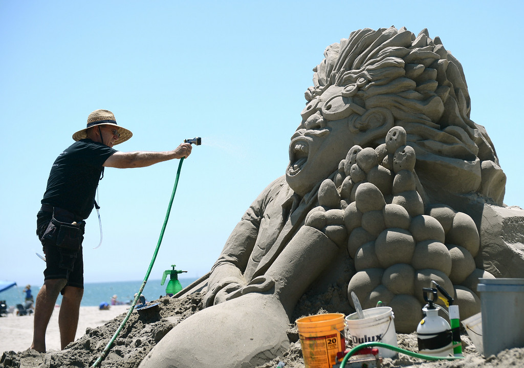 . Artists took to the beach at Belmont Shore for the 82nd Annual Sand Sculpture Contest Saturday, August 16, 2014, Long Beach, CA.    Greg Lebon, of Torrance, sprays a light mist of water as he works his sculpture. Photo by Steve McCrank/Daily Breeze