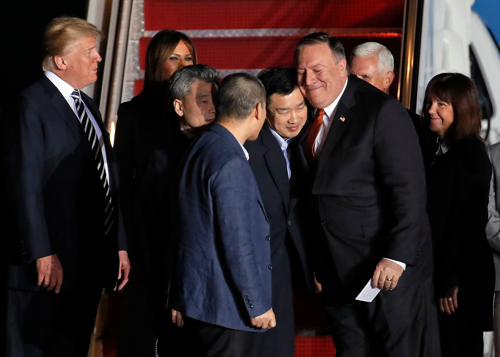 . President Donald Trump, left, with first lady Melania Trump, watch Secretary of State Mike Pompeo, right, embrace former North Korean detainee Tony Kim, with Kim Hak Song, third from left, and Kim Dong Chul, front, upon their arrival, Thursday, May 10, 2018, at Andrews Air Force Base, Md. The three Korean-Americans were greeted by Trump beneath a giant American flag after they returned to the mainland U.S. early Thursday. Vice President Mike Pence and his wife Karen, right, also greeted their arrival. (AP Photo/Alex Brandon)