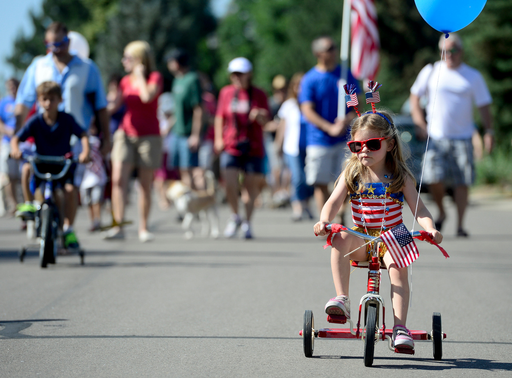 ". Amber Bernard, 4, rides in the annual Fourth of July parade in The Greens neighborhood Friday morning, July 04, 2014. This was the 13th year for the parade according to organizer Jean Goldstein who participated in similar July Fourth celebrations organized by her father when she was growing up in Akron, Ohio. ""It\'s one of my favorite memories of all time,\"" she said. (Lewis Geyer/Times-Call)"