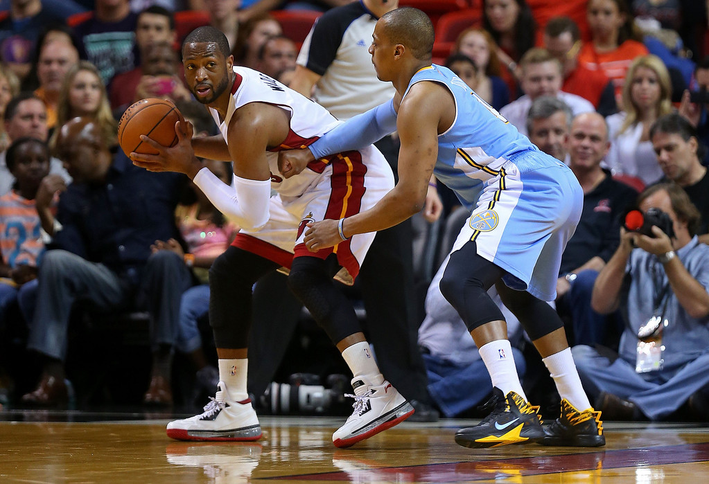 . MIAMI, FL - MARCH 14: Dwyane Wade #3 of the Miami Heat is defended by Randy Foye #4 of the Denver Nuggets during a game  at American Airlines Arena on March 14, 2014 in Miami, Florida. (Photo by Mike Ehrmann/Getty Images)