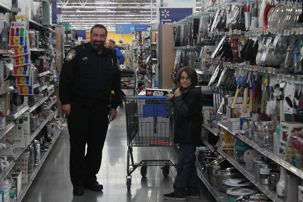 . Kristi Garabrandt � The News-Herald� <br> Officers from Willowick Police Department take 14 students from Royalview elementary school Christmas shopping at Walmart during their third annual Christmas with the Blue.  Following the shopping available spouses of the officers joined in the fun by helping students wrap their gifts.