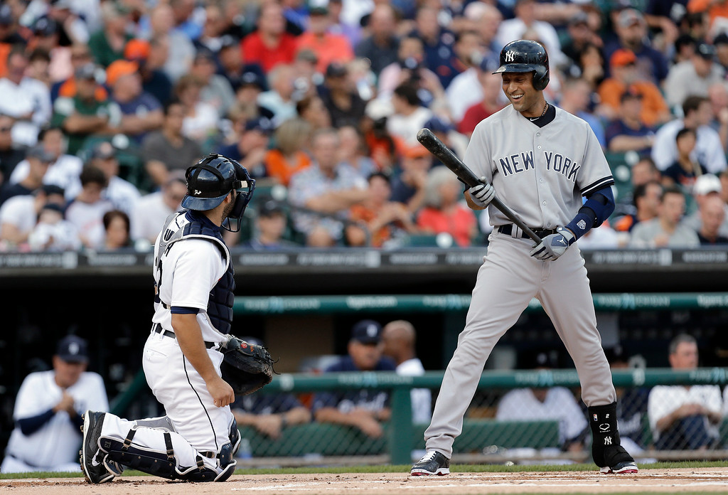 . New York Yankees, Derek Jeter, right, laughs with Detroit Tigers catcher Alex Avila while batting in the first inning of a baseball game in Detroit, Wednesday, Aug. 27, 2014. (AP Photo/Paul Sancya)
