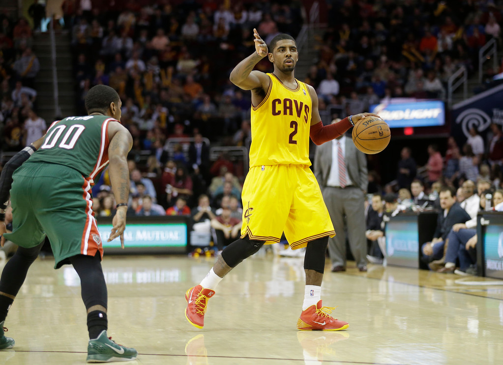 . Cleveland Cavaliers\' Kyrie Irving (2) signals his teammates against Milwaukee Bucks\' O.J. Mayo (00) in the second half of an NBA basketball game Friday, Dec. 20, 2013, in Cleveland. (AP Photo/Mark Duncan)