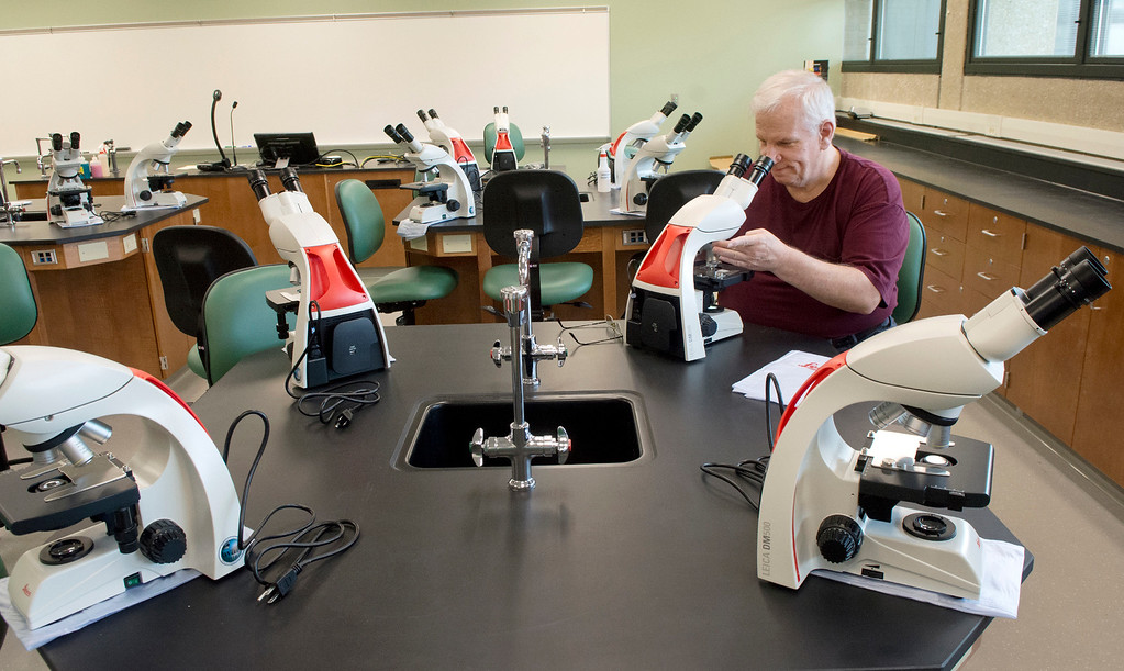 . Lakeland Community College Biology Instructor Tom Rhyand uses one of the new Leica compound microscopes in one of the newly renovated science labs in August 2015. (News-Herald file)