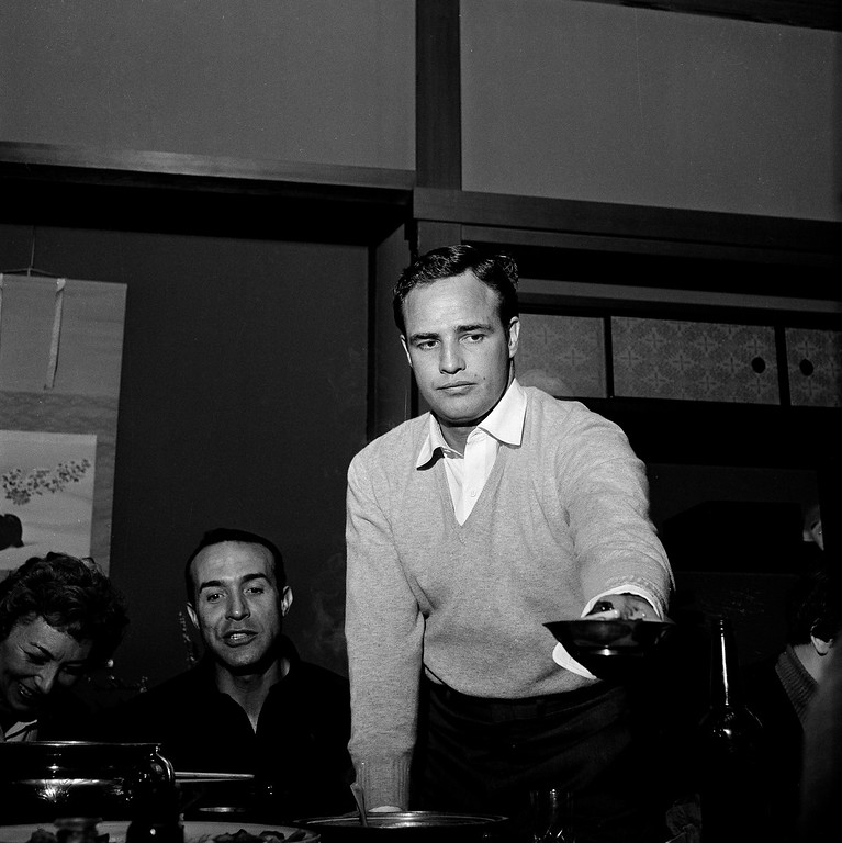 ". Actor Marlon Brando dishes up a bowl of soup at a cast party dinner for the cast of ""Sayonara\"" in Kyoto, Japan, Jan. 21, 1957. In the background at left, actor Ricardo Montalban looks on. (AP Photo)"