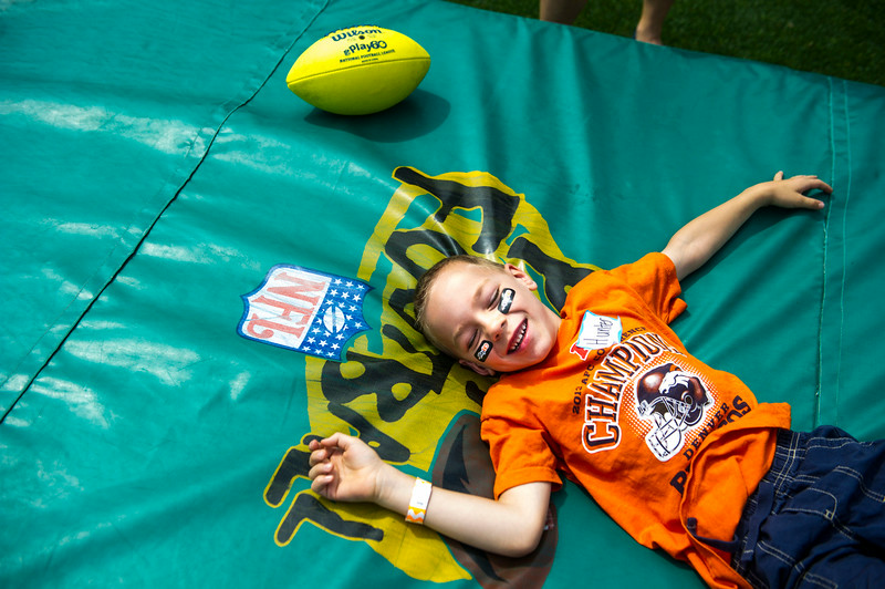 . Hunter Kozney, 7, of Arvada, smiles after making a leaping catch during the National Sports Center for the Disabled\'s Denver Broncos Ability Clinic at Sports Authority Field at Mile High on Tuesday, July 08, 2014 in Denver, CO. (Photo by Kent Nishimura/The Denver Post)