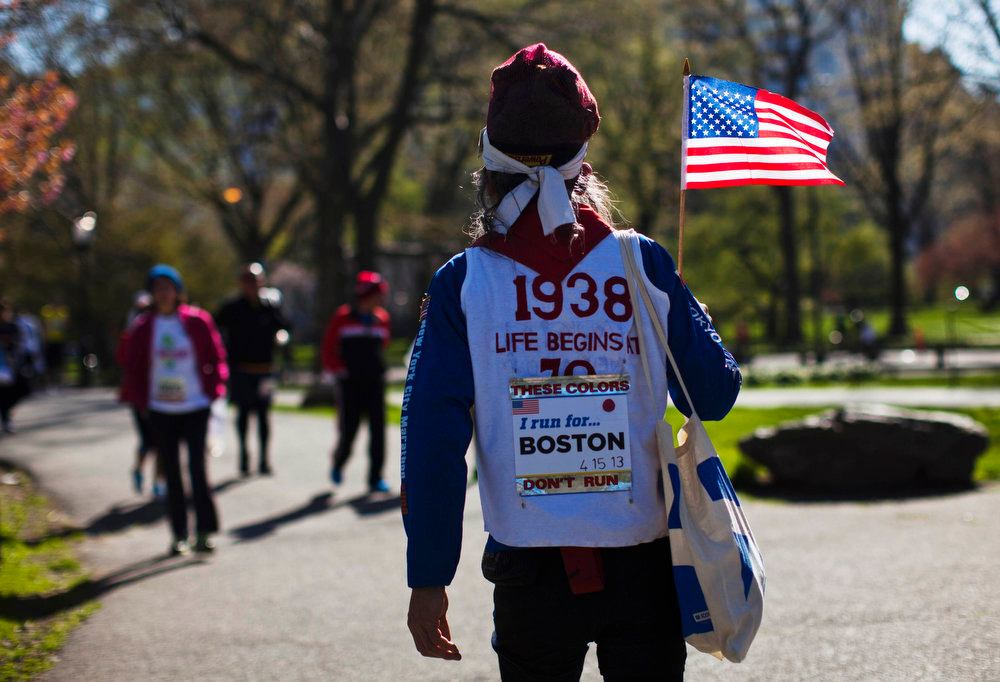 Description of . A participant wearing a singlet in tribute to victims of the Boston Marathon bombing, holds a miniature U.S. flag after taking part in a race organized by the New York Road Runners at Central Park in New York April 21, 2013. The New York Police Department has tightened security during the race in response to the bomb attacks at the Boston Marathon, according to local media. REUTERS/Eduardo Munoz
