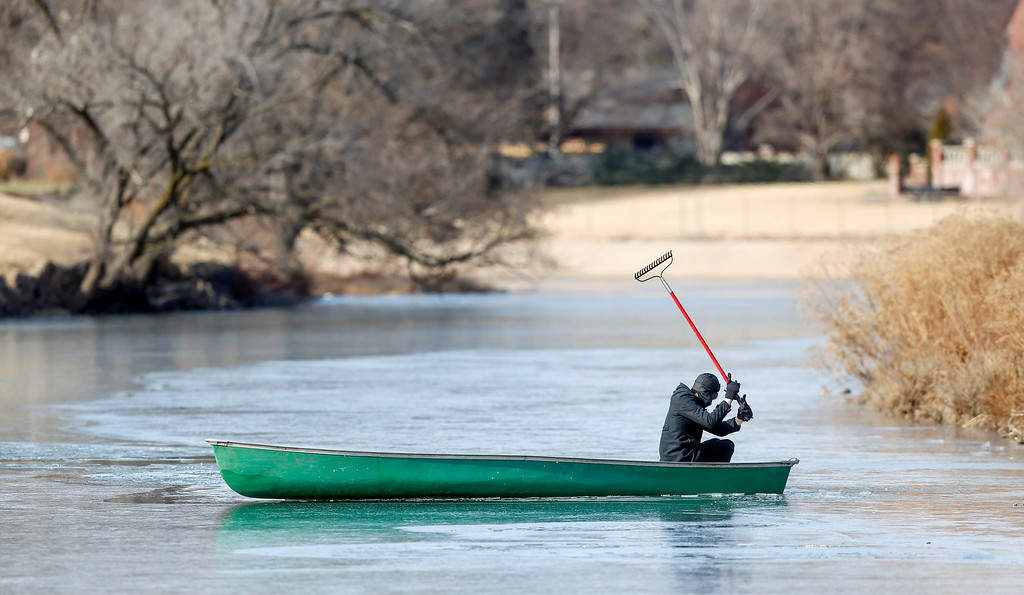 . Tim Christmore uses a rake to get his canoe through the ice-covered Little Arkansas River in Wichita, Kan., on Tuesday, Dec. 26, 2017. (Fernando Salazar/The Wichita Eagle via AP)