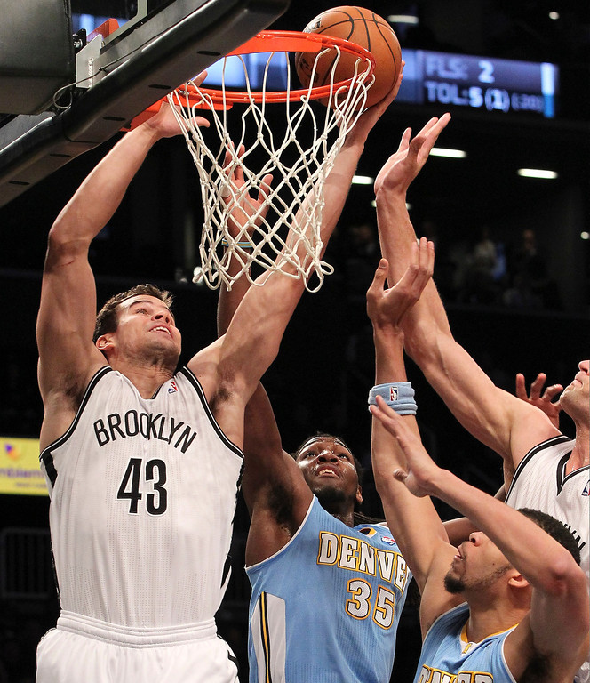 . Brooklyn Nets\' Kris Humphries (43) shoots past Denver Nuggets\' Kenneth Faried (35) and JaVale McGee during the first half of an NBA basketball game on Wednesday, Feb. 13, 2013, at Barclays Center in New York. (AP Photo/Mary Altaffer)