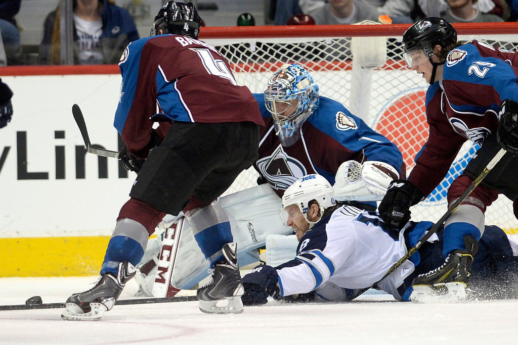 . Bryan Little (18) of the Winnipeg Jets hits the ice in front of Semyon Varlamov (1) of the Colorado Avalanche as Tyson Barrie (4) and Nathan MacKinnon (29) defend during the Avs\' 3-2 win. (Photo by AAron Ontiveroz/The Denver Post)