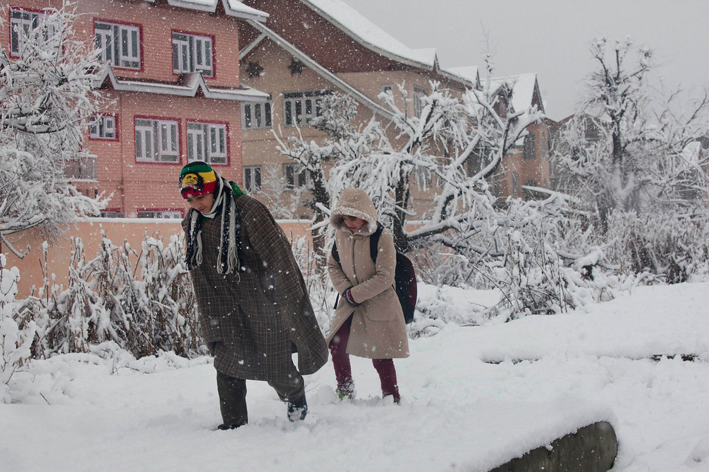 . Kashmiri children walk on a snow-covered road as fresh snow falls in Srinagar, India, Tuesday, Dec. 31, 2013. Snowfall in the Indian portion of Kashmir has disrupted power supply, air traffic and road traffic between Srinagar and Jammu, the summer and winter capitals of India\'s Jammu-Kashmir state, according to news reports. (AP Photo/Dar Yasin)