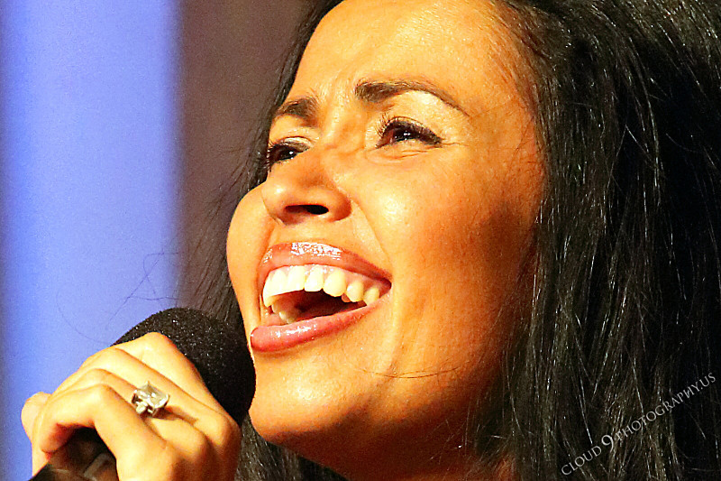 AMER-CMM 00024 A tight crop of Adrianne Mace's face as she sings before a church audience by Peter J Mancus.JPG