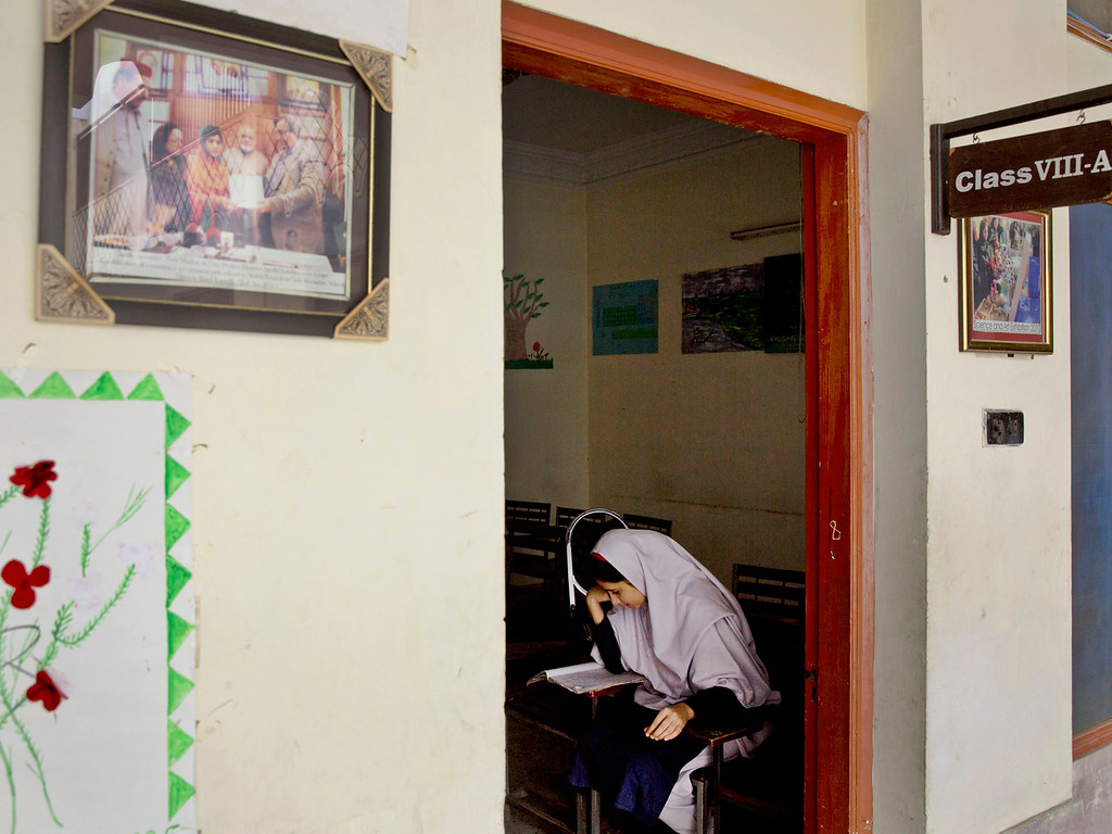 . A Pakistani girl studies at Malala Yousufzai\'s old school in Mingora, Swat Valley, Pakistan on Saturday, Oct 5, 2013. Only a single picture showing Malala receiving an award  stayed on the wall, a giant poster of her that once emblazoned the wall of the assembly hall has been removed. The school made no plans to recognize the anniversary of Malala\'s shooting by Taliban because teachers and students are afraid.  (AP Photo/Anja Niedringhaus)