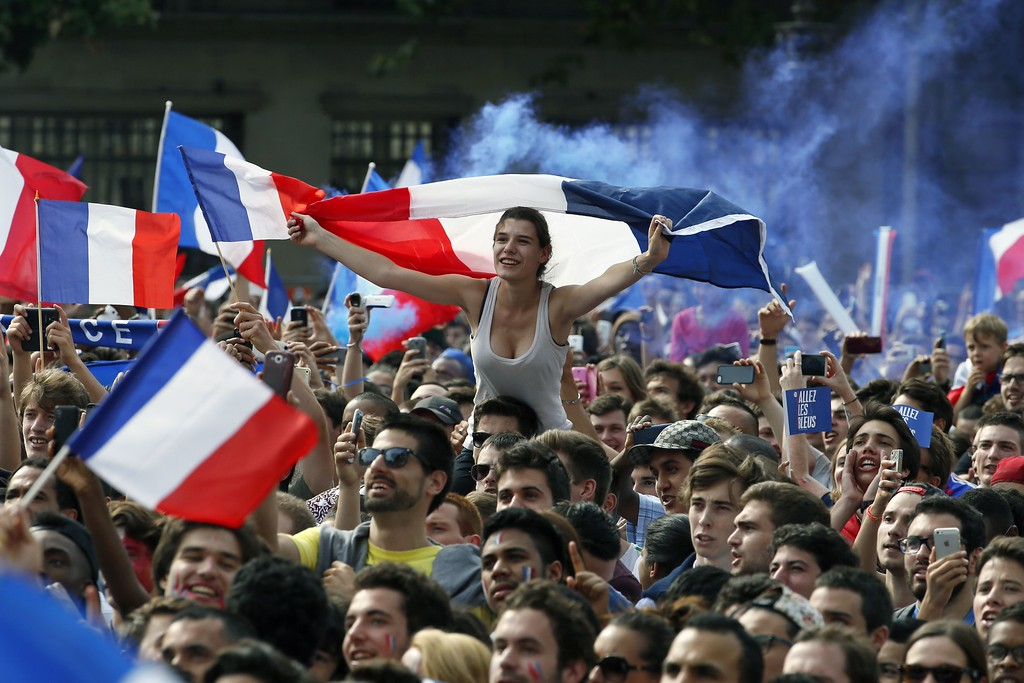 . TOPSHOTS France fans wave French flags as they watch the 2014 FIFA World Cup quarter final football match between France and Germany on a giant screen at the Hotel de Ville (City Hall) in Paris on July 4, 2014. AFP PHOTO / PATRICK KOVARIKPATRICK KOVARIK/AFP/Getty Images