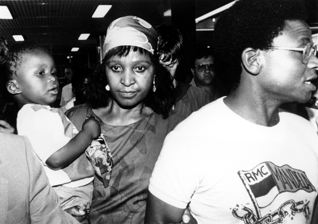 . Anti-Apartheid activist Winnie Mandela, carrying her 2-year-old granddaughter Zondwa, arrives at Jan Smuts airport in Johannesburg, South Africa on Dec. 30, 1985. Mandela is intent on going back to her home in Soweto township in defiance of the ban that prohibits her from being in the area. She is arriving from Cape Town where she was visiting her husband, jailed leader of the ANC Nelson Mandela. (AP Photo/Greg English)