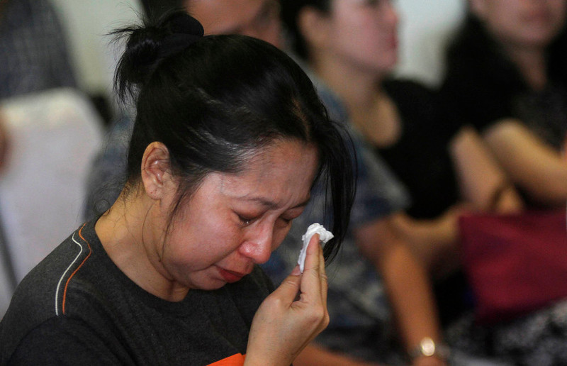 . One of relatives and next-of-kin of passengers on the AirAsia flight QZ8501 wipes tears as she awaits the latest news on the search of the missing jetliner at Juanda International Airport in Surabaya, East Java, Indonesia, Monday, Dec. 29, 2014. Search planes and ships from several countries on Monday were scouring Indonesian waters over which an AirAsia jet disappeared, more than a day into the region\'s latest aviation mystery. AirAsia Flight 8501 vanished Sunday in airspace thick with storm clouds on its way from Surabaya, Indonesia, to Singapore. (AP Photo/Trisnadi Marjan)