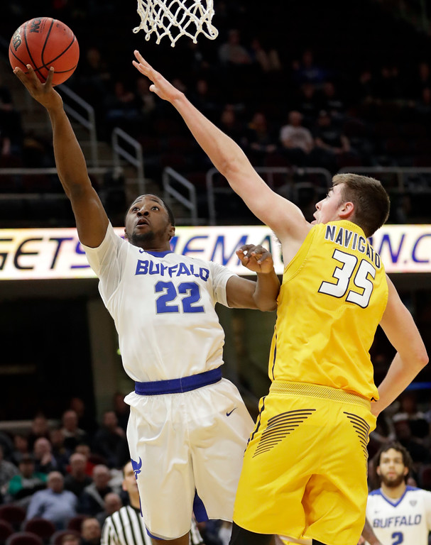 . Buffalo\'s Dontay Caruthers (22) shoots against Toledo\'s Nate Navigato (35) during the first half of an NCAA college basketball championship game of the Mid-American Conference tournament, Saturday, March 10, 2018, in Cleveland. (AP Photo/Tony Dejak)