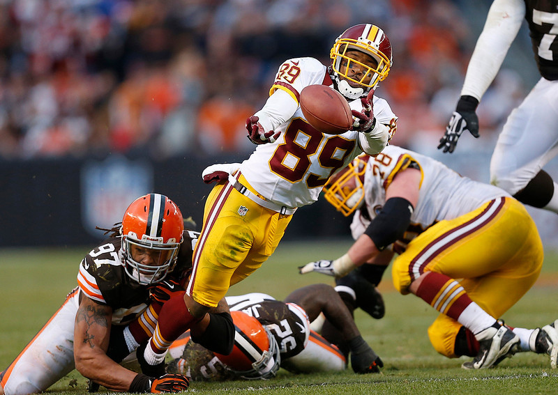 . Washington Redskins wide receiver Santana Moss (89) fumbles after being hit by Cleveland Browns defensive end Jabaal Sheard (97) and linebacker D\'Qwell Jackson (52) in the fourth quarter of an NFL football game in Cleveland, Sunday, Dec. 16, 2012. (AP Photo/Rick Osentoski)