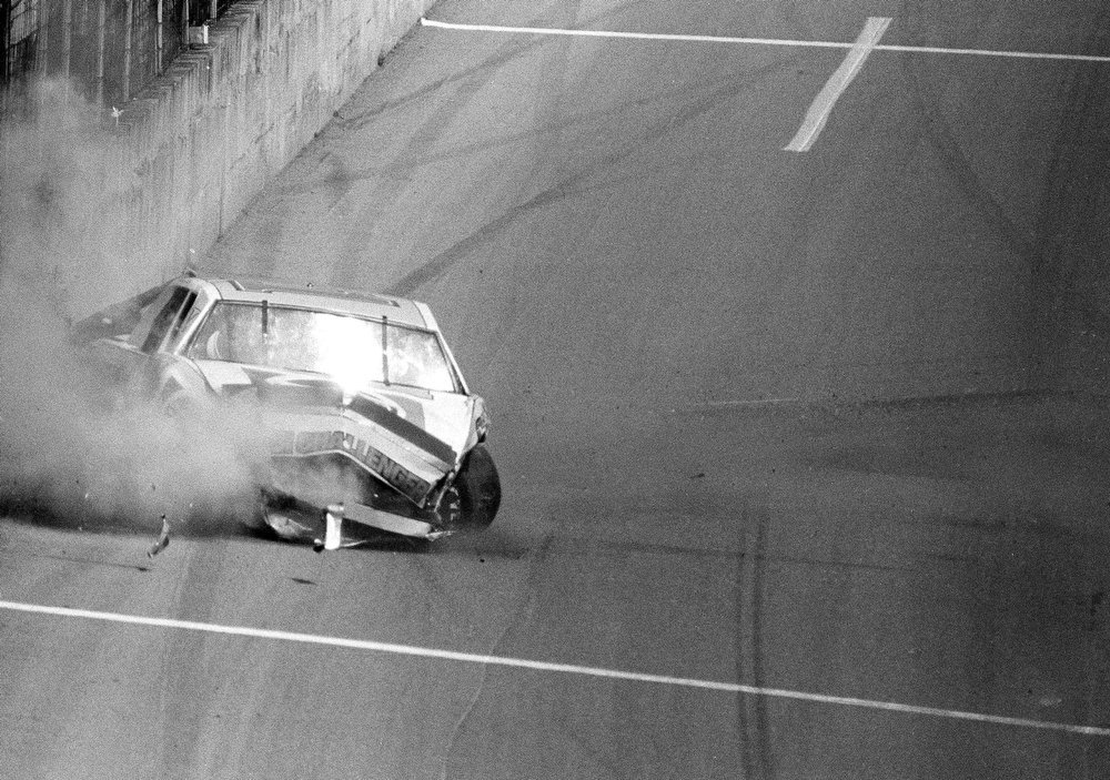 Description of . Darrell Waltrip of Franklin, Tenn., hits the wall coking down the straight at the Daytona International Speedway during the 25th annual Daytona 500 at Daytona Beach, Fla., Feb. 20, 1983.  Waltrip had to be taken from his wrecked Chevrolet and taken away in an ambulance but reports indicate his injuries were not serious.   (AP Photo/Glenda Dixon)