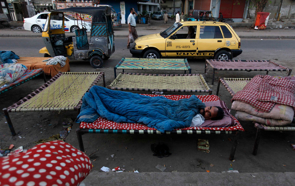 . A man sleeps on a charpoy bed along a road, near a railway station in Karachi April 1, 2013. Charpoy bed guesthouses are only setup at night from 9pm to 7am for the homeless, passengers and drivers, charging about 40 Pakistani rupees ($0.40) per night. REUTERS/Akhtar Soomro