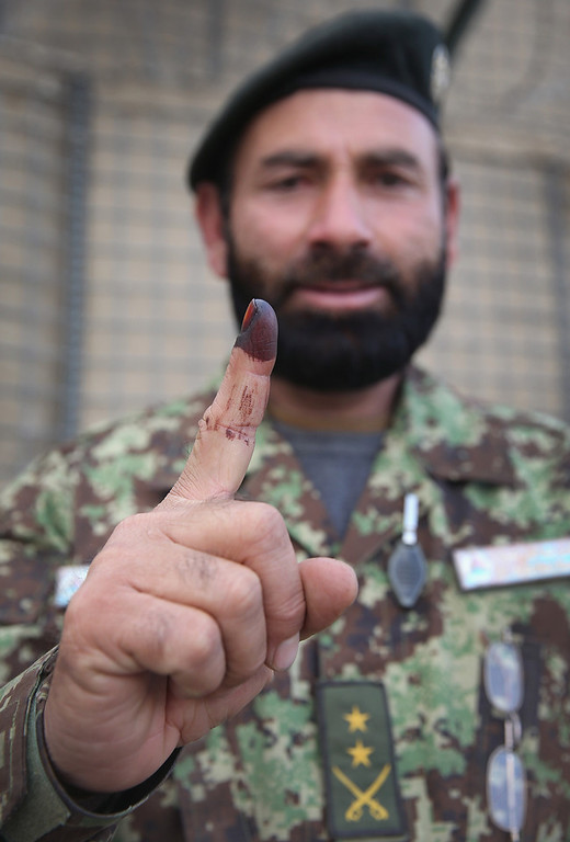 . A soldier with the Afghan National Army (ANA) shows off the ink on his finger, proof that he voted, while working in the tactical operations center at Camp Maiwand on April 5, 2014 near Pul-e Alam, Afghanistan. Today, despite threats of Taliban violence, Afghans went to the polls in large numbers to select a successor to current President Hamid Karzai.  (Photo by Scott Olson/Getty Images)