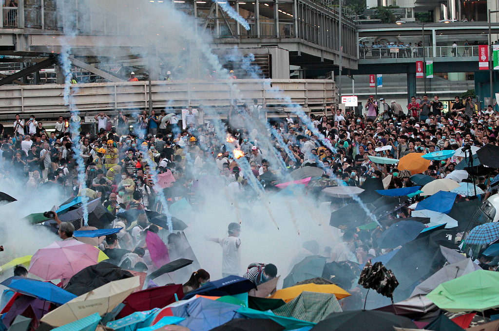 . Riot police launch tear gas into the crowd as thousands of protesters surround the government headquarters in Hong Kong Sunday, Sept. 28, 2014. Hong Kong police used tear gas and warned of further measures as they tried to clear thousands of pro-democracy protesters gathered outside government headquarters in a challenge to Beijing over its decision to restrict democratic reforms for the city. (AP Photo/Wally Santana, File)