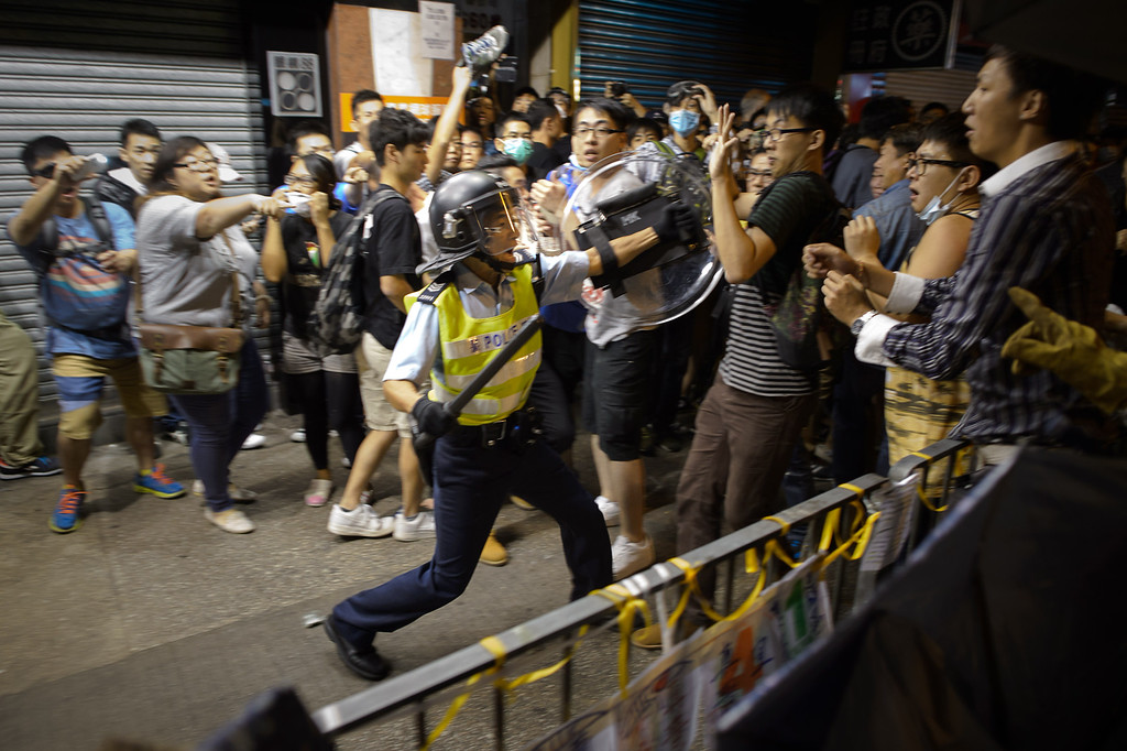 . A policeman holding a baton advances towards pro-democracy protesters as they clash on a street in the Mong Kok district of Hong Kong early on October 19, 2014. Hong Kong\'s embattled government said it will open talks with student demonstrators on October 21, after three nights of violent clashes between police and protesters who have paralysed parts of the city with mass pro-democracy rallies.   AFP PHOTO / Ed JonesED JONES/AFP/Getty Images