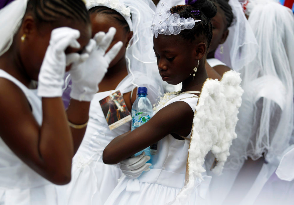 Description of . Girls from the Garifuna ethnic people are dressed in white while participating in a procession to mark the death of Jesus Christ on Good Friday during Holy Week in Livingston, 350 km (217 miles) north east Guatemala City March 29, 2013. Holy Week is celebrated in many Christian traditions during the week before Easter. Garifuna are descendants of Carib and Arawak indians and West African slaves who settled along the Atlantic coast of Guatemala, Belize, Nicaragua and Honduras after the British deported them from St. Vincent in the 18th century. REUTERS/Jorge Dan Lopez