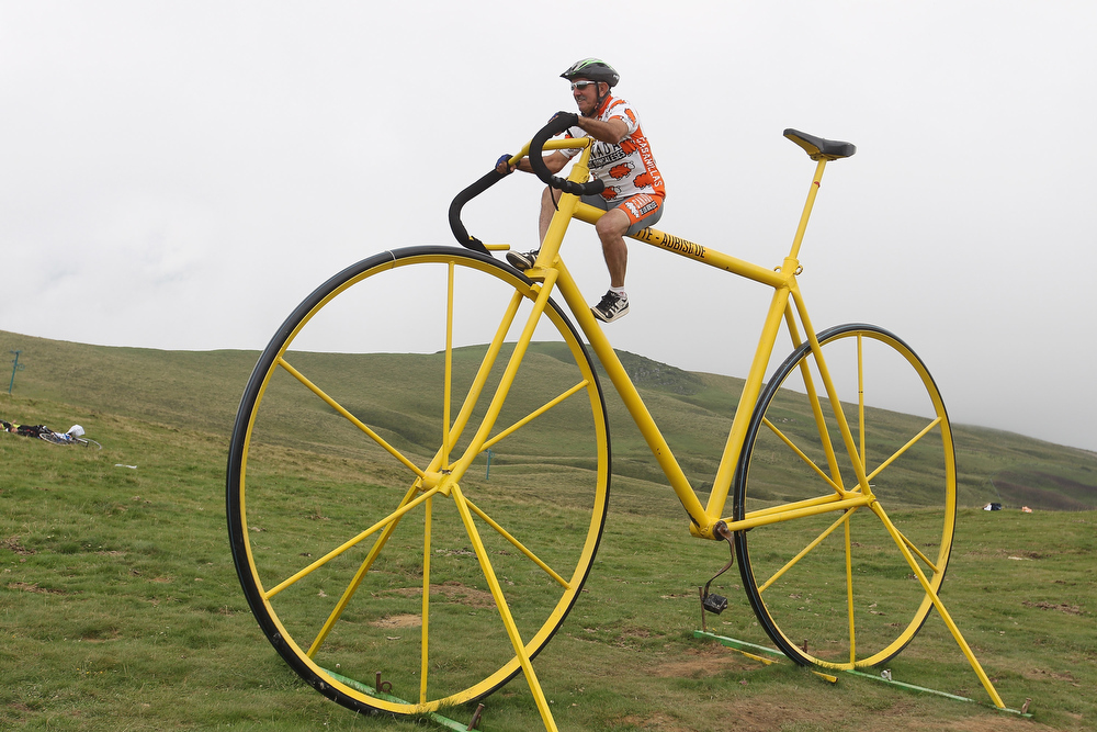 Description of . A cycling fan sits on a giant bike sculpture on the summit of the Col d\'Aubisque during Stage 13 of the 2011 Tour de France from Pau to Lourdes  on July 15, 2011 in Lourdes, France.  (Photo by Michael Steele/Getty Images)