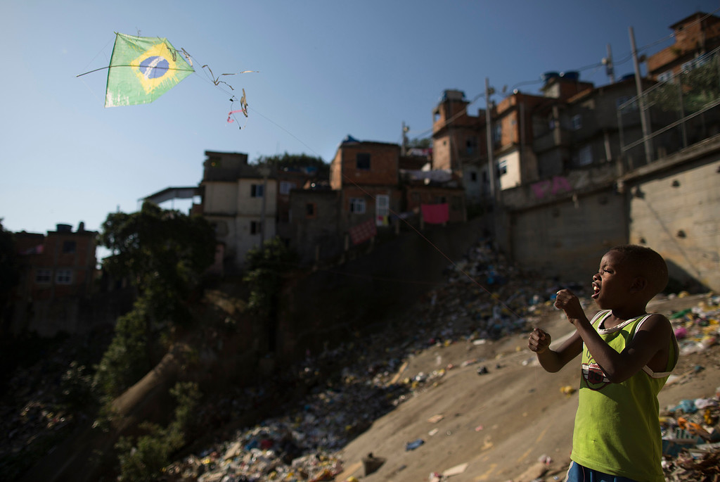 . In this Monday, June 2, 2014 photo, a youth flies a kite in the likeness of Brazil\'s flag on a hillside in the Mangueira slum in Rio de Janeiro, Brazil. Brazil is hosting this year\'s World Cup soccer tournament that starts next week. (AP Photo/Leo Correa)
