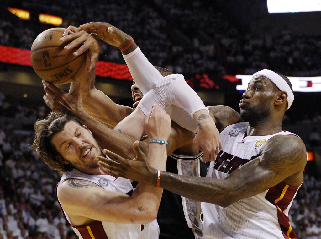 . Mike Miller (L) and LeBron James (R) of the Miami Heat vie for a rebound with Tim Duncan (C) of the San Antonio Spurs during the first half in Game 6 of the NBA Finals at the American Airlines Arena June 19, 2013 in Miami, Florida.  BRENDAN SMIALOWSKI/AFP/Getty Images
