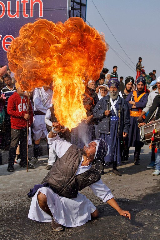 . A Sikh devotee blows fire during a procession ahead of the birth anniversary of Guru Gobind Singh in Jammu, India, Saturday, Jan. 4, 2014. The birth anniversary of Guru Gobind Singh, the tenth Sikh guru, will be marked on Jan. 7 this year. (AP Photo/Channi Anand)