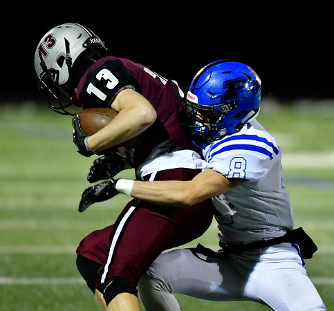 11/21/2018 Mike Orazzi | Staff Plainville's Brendan Quilter (8) and Farmington's Niko Bouzakis (13) during Wednesday night's football game at Farmington High School.