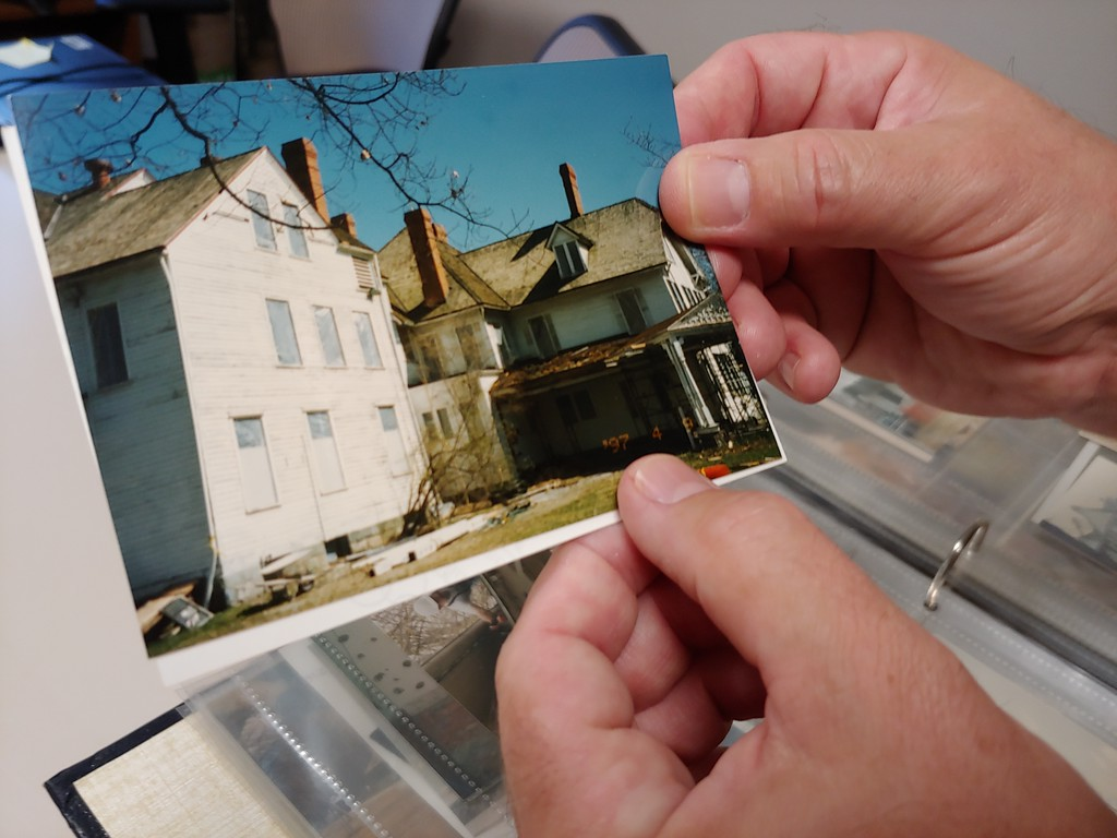 . Todd Arrington, site manager at James A. Garfield National Historic Site, shows photos of the renovation of the home. (Betsy Scott, The News-Herald)
