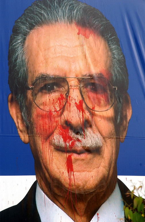 . Former dictator Efrain Rios Montt is seen in a poster splattered with red paint, sympbolizing blood, in Guatemala City, Tuesday, Oct 7, 2003. Human rights groups say the ex-general was responsible for some of the worst atrocities committed during Guatemala\'s 36- year civil war. Rios Montt is running for president in the Nov. 9 elections and insists he has put his dark past behind him. (AP Photo/ Rodrigo Abd)