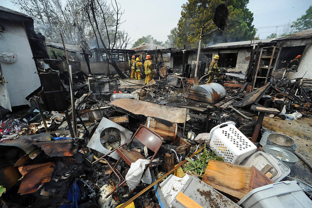 . Firefighters search for hotspots after a structure fire damaged two homes in the 17800 block of Vanowen St. in Reseda, CA April 10, 2014.(Andy Holzman/Los Angeles Daily News)