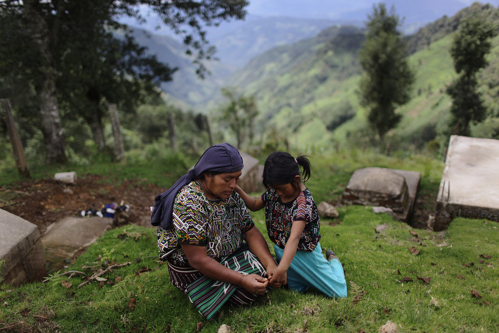 """. In this photo taken July 23, 2011, Juana Matom rests with her daughter at the Vijolom II cemetery in Nebaj, Guatemala. Guatemalan soldiers allegedly killed Matom\'s brother and father in Sept. 1982 during a raid on the community of Vivitz in Nebaj municipality. Twenty-nine years later, in June 2011, the Public Ministry brought charges against Gen. Hector Mario Lopez Fuentes in connection with the planning and ordering of bloody military operations that were part of the military plan coined \""""Victoria 82,\"""" among other crimes during his time as the Defense Ministry\'s Chief of Staff, including the extermination of residents in villages within the municipality of Nebaj during the government of Efrain Rios Montt (1982-1983). (AP Photo/Rodrigo Abd)"""