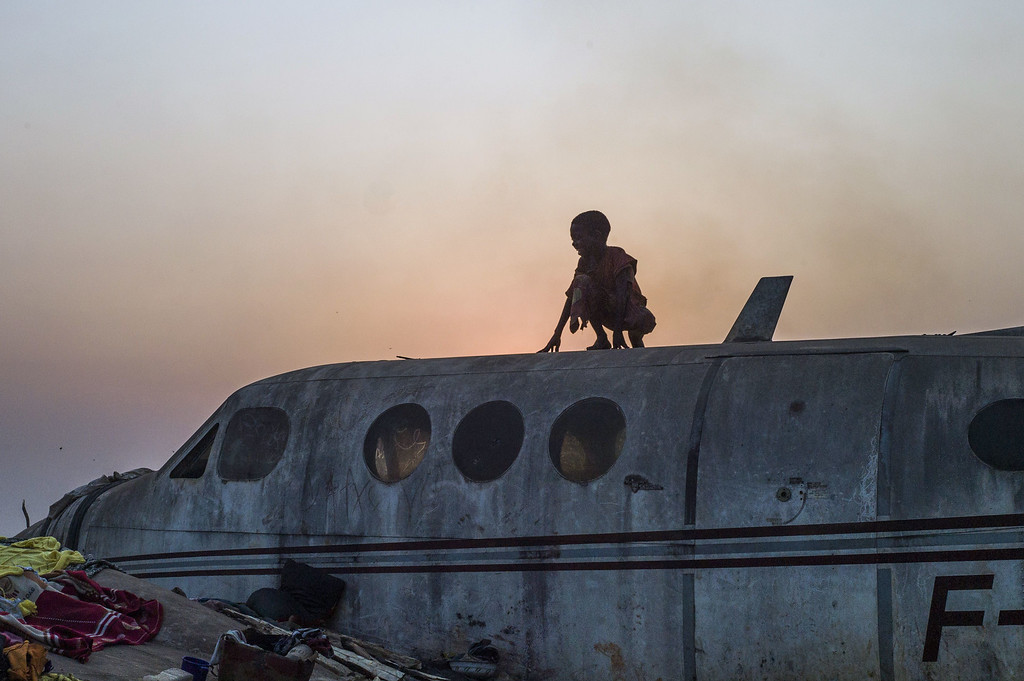 . A boy stands on an airplane in the Christian Mpoko refugee camp on February 20, 2014 during sunset, in Bangui, Central African Republic. AFP PHOTO / FRED  DUFOUR/AFP/Getty Images