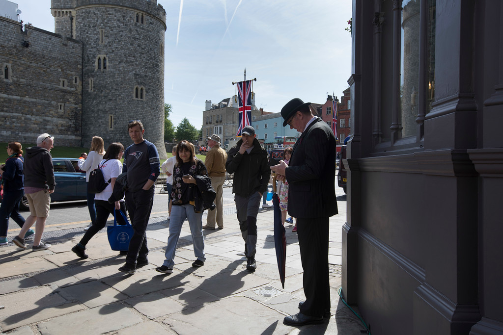 . A man wearing a bowler hat looks at his mobile phone in front of Windsor castle, England, Friday, May 18, 2018. Preparations continue in Windsor ahead of the royal wedding of Britain\'s Prince Harry and Meghan Markle Saturday May 19. (AP Photo/Peter Dejong)