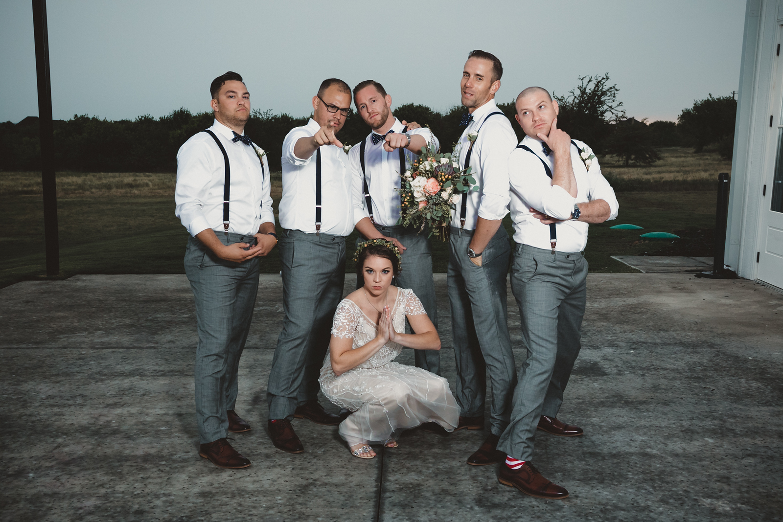a groom pointing at the camera with his bride and groomsmen humorously posing around him
