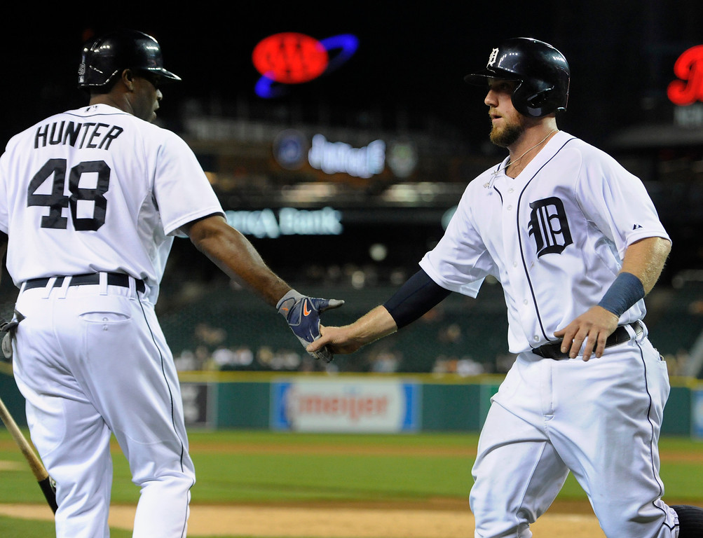 . Detroit Tigers\' Bryan Holaday, right, is greeted by Torii Hunter after Holaday scored during the fifth inning of a baseball game against the San Francisco Giants on Friday, Sept. 5, 2014, in Detroit. (AP Photo/Jose Juarez)