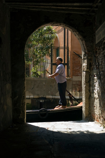 Gondolier framed by an archway, Venice, Italy