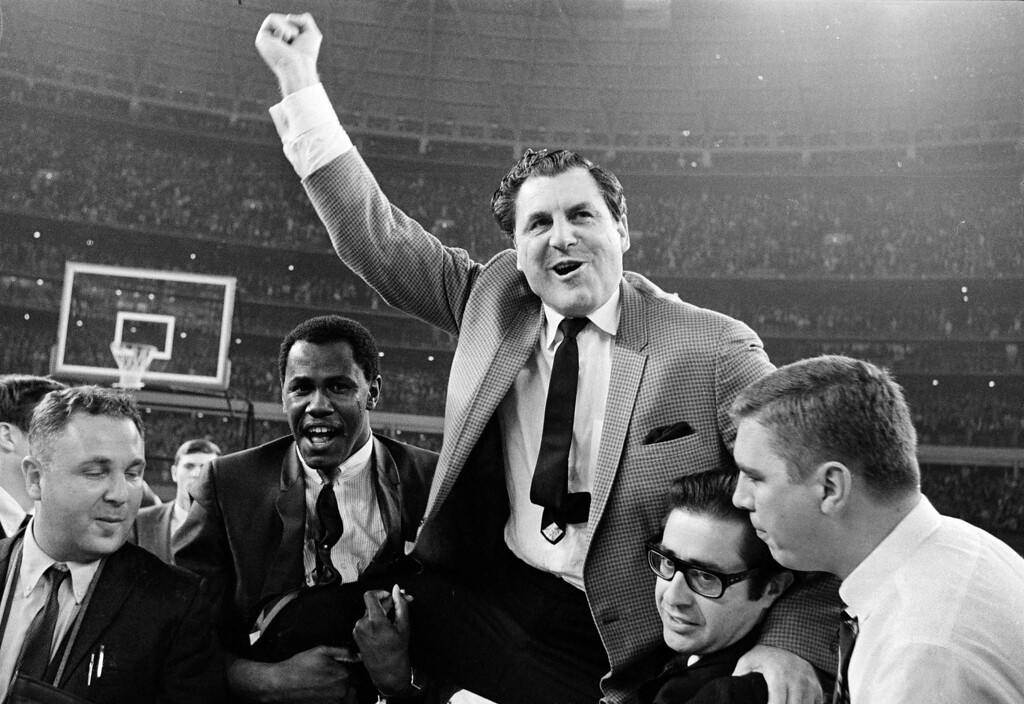 . Guy V. Lewis, University of Houston basketball coach, lets out a war whoop as he is carried to the dressing room by happy fans after the Houston Cougars\' upset over the UCLA Bruins in the Houston Astrodome, Jan. 20, 1968. (AP Photo/Ed Kolenovsky)