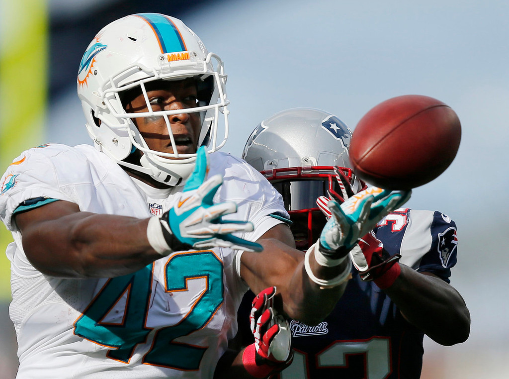 . New England Patriots free safety Devin McCourty, right, breaks up a pass intended for Miami Dolphins tight end Charles Clay (42) in the first half of an NFL football game on Sunday, Oct. 27, 2013, in Foxborough, Mass. (AP Photo/Michael Dwyer)