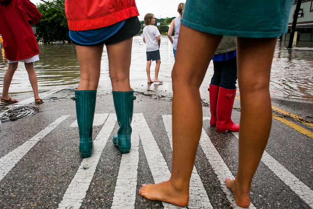 . AUSTIN, TX - MAY 25:   Onlookers watch as a street floods from days of heavy rain on May 25, 2015 in Austin, Texas. Texas Gov. Greg Abbott toured the damage zone where one person is confirmed dead and at least 12 others missing in flooding along the Rio Blanco, which reports say rose as much as 40 feet in places, caused by more than 10 inches of rain over a four-day period. The governor earlier declared a state of emergency in 24 Texas counties.  (Photo by Drew Anthony Smith/Getty Images)
